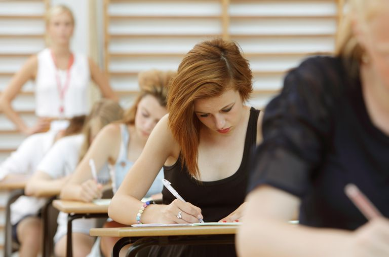 Students taking exam, teacher in background