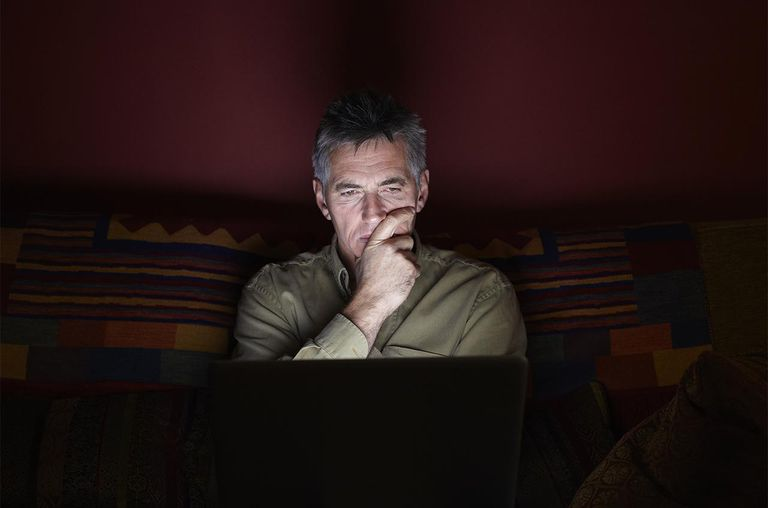 Man sat on sofa using laptop at night