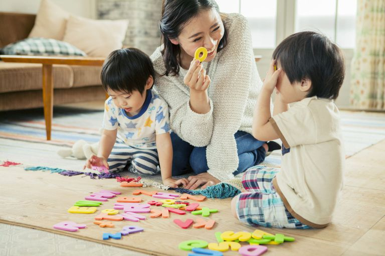 A woman playing with foam letters with kids