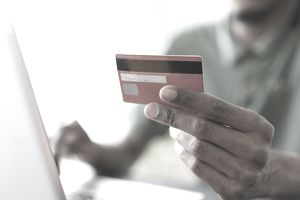 Cropped image of man holding credit while shopping online