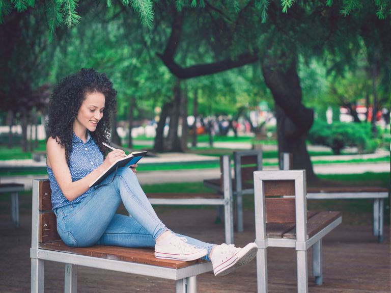 Young woman sitting on a bench and writing notes in notebook