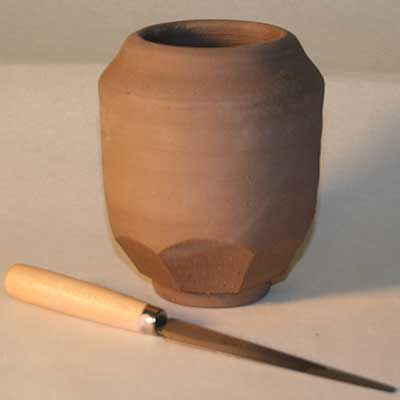 Pottery form enhanced by facets cut from lower portion of thrown pot with trimmed foot ring.