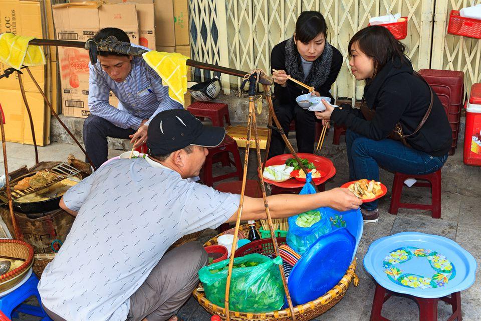 Street food vendor and patrons in Hanoi, Vietnam