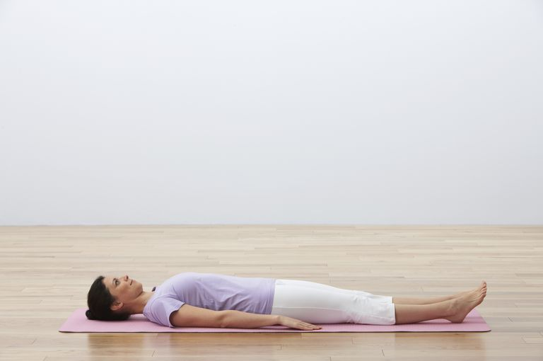 Woman lying on her back on exercise mat, side view