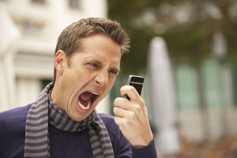 Angry man shouting at phone unwanted call