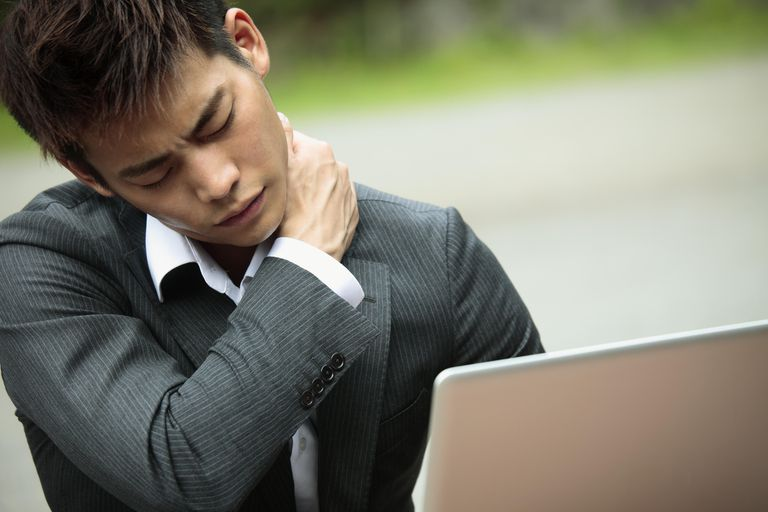 Man working on laptop rubbing his neck