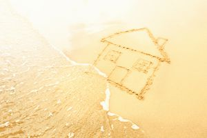 House in sand washed away by waves