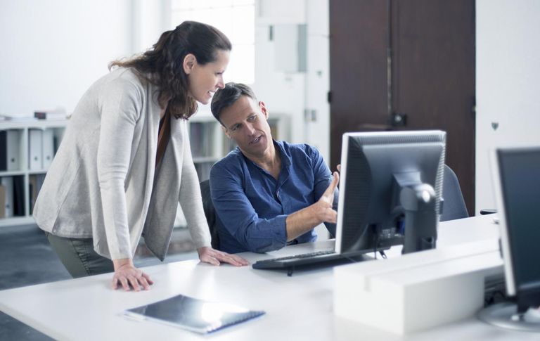 man and woman talking in front of computer at office