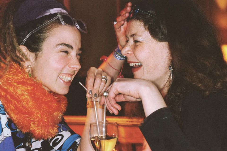 Two young women drinking out of same glass