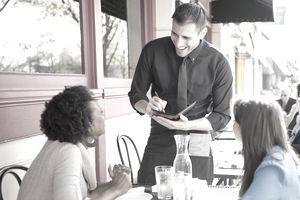 Server taking orders at sidewalk cafe