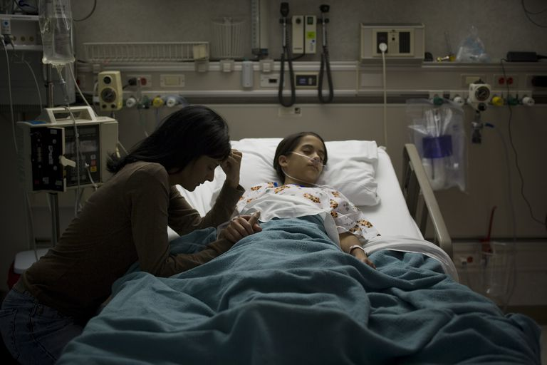 High angle view of a girl lying on a hospital bed with her mother holding her hand beside her