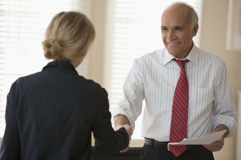 Hispanic businessman shaking hands with co-worker