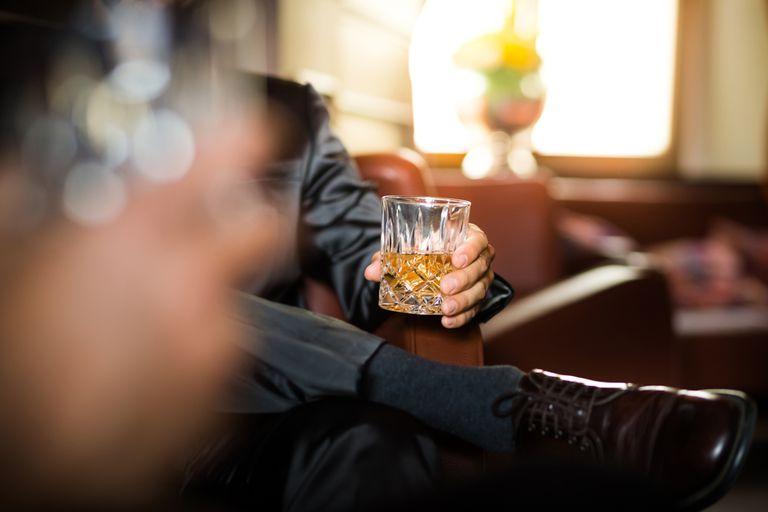 Businessman holding whiskey glass