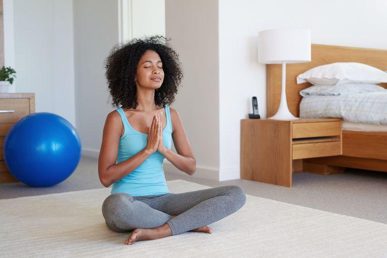Woman doing yoga in her bedroom
