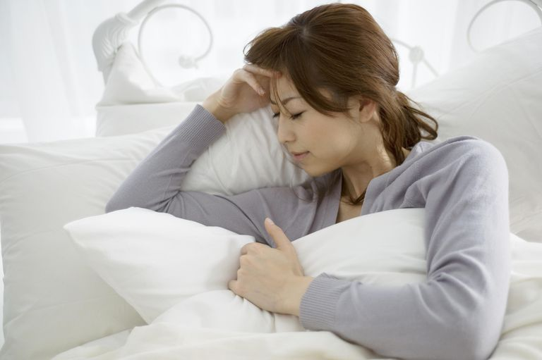 The woman who suffers from a headache in a bed