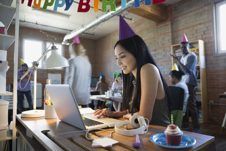 Businesswoman wearing birthday party hat at laptop