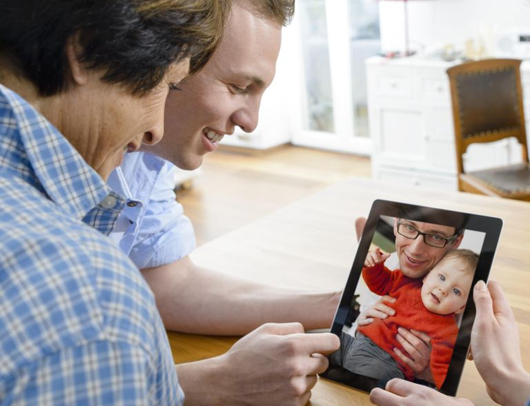 Senior woman and young man looking at image of father and baby son on digital tablet