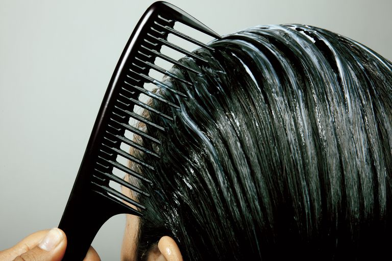 combing conditioner through hair, close up