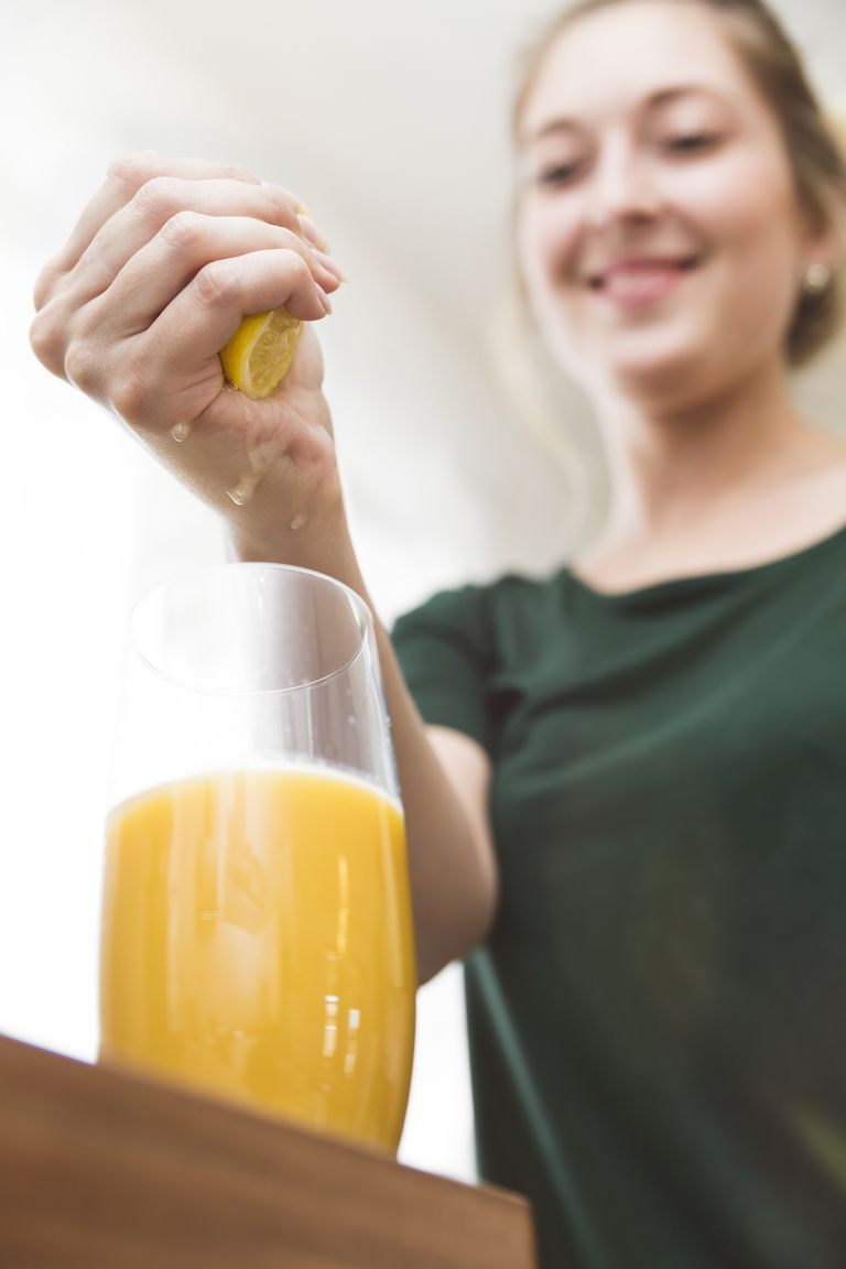 Woman squeezing lemon juice into glass of homemade smoothie