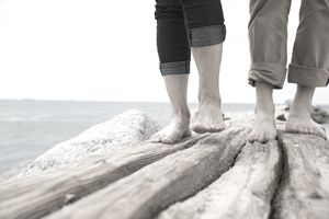 Close up bare feet of couple on ocean jetty