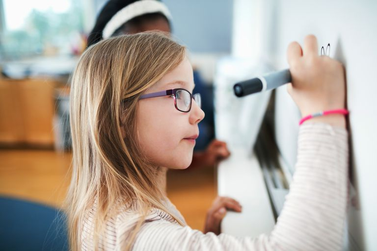 Close-up of girl wearing eyeglasses writing on whiteboard in classroom