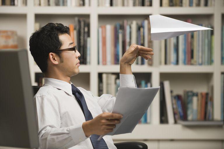 Asian businessman throwing paper airplane