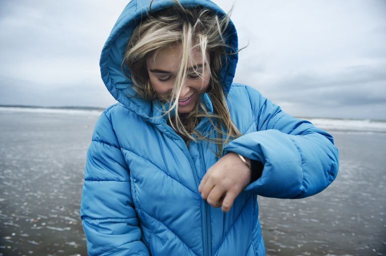 Woman on beach, closing zipper of hooded jacket.