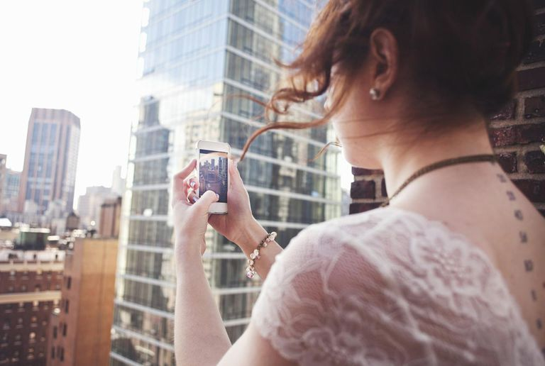 Young woman using smartphone to photograph Manhattan