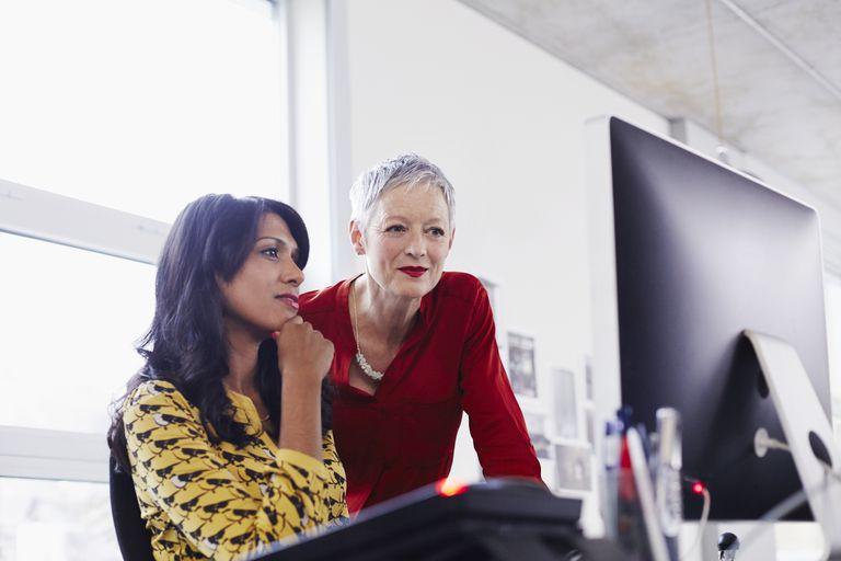 Mature business woman mentoring younger employee.