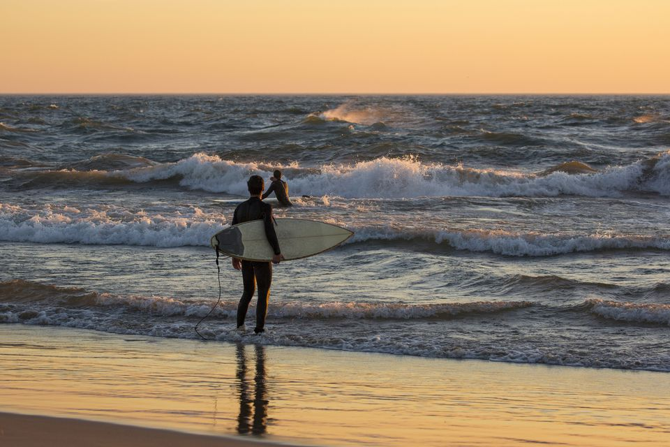 Surfers on Lake Michigan beach at sunset, Grand Haven, Ottawa County, Michigan, USA