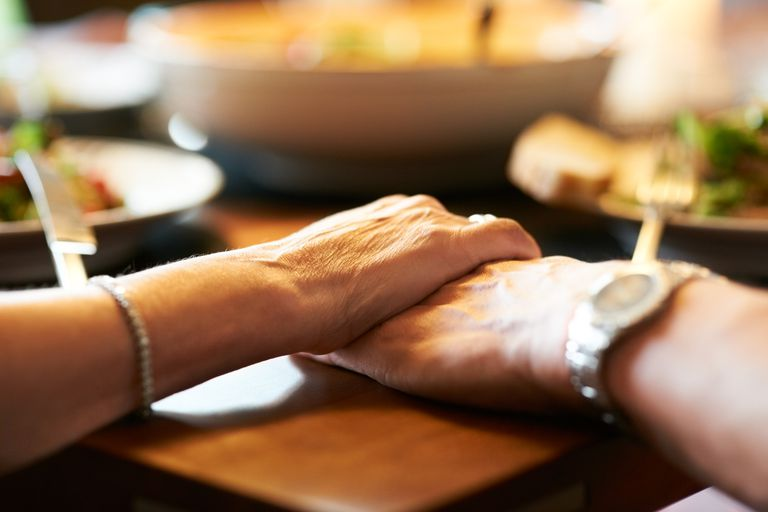 Close up of holding hands at dinner table