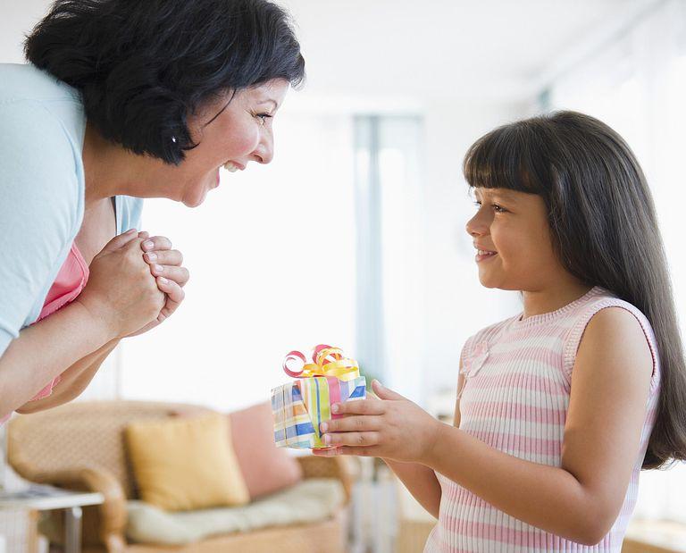 Niña latina dando un regalo su mamá