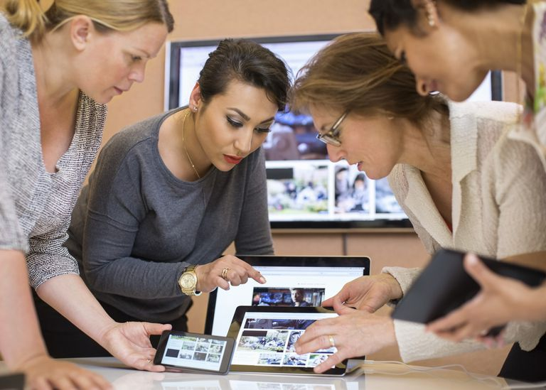 Female photo editors discussing over digital tablet in creative office