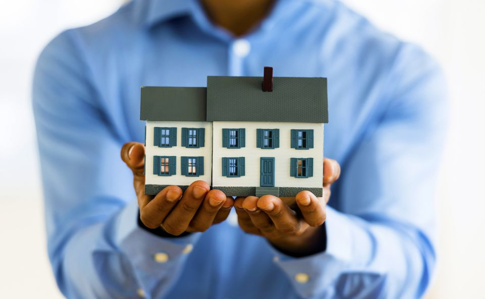 Man holding a miniature house in his hands
