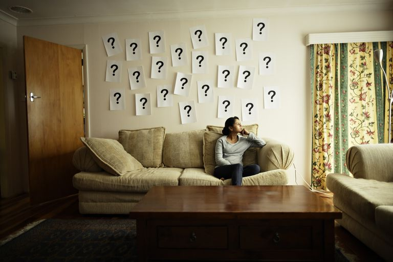 Woman Sitting in Front of Question Marks