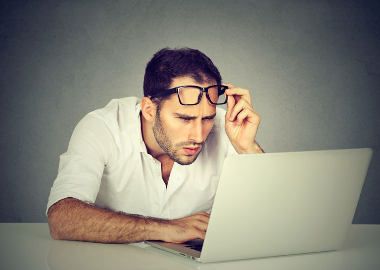 man with glasses having eyesight problems with laptop