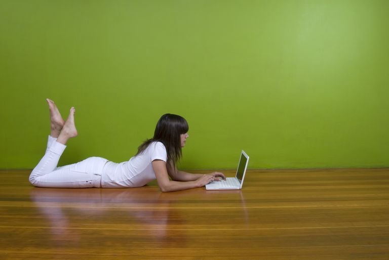 Picture of a woman using a Mac computer while lying on the floor