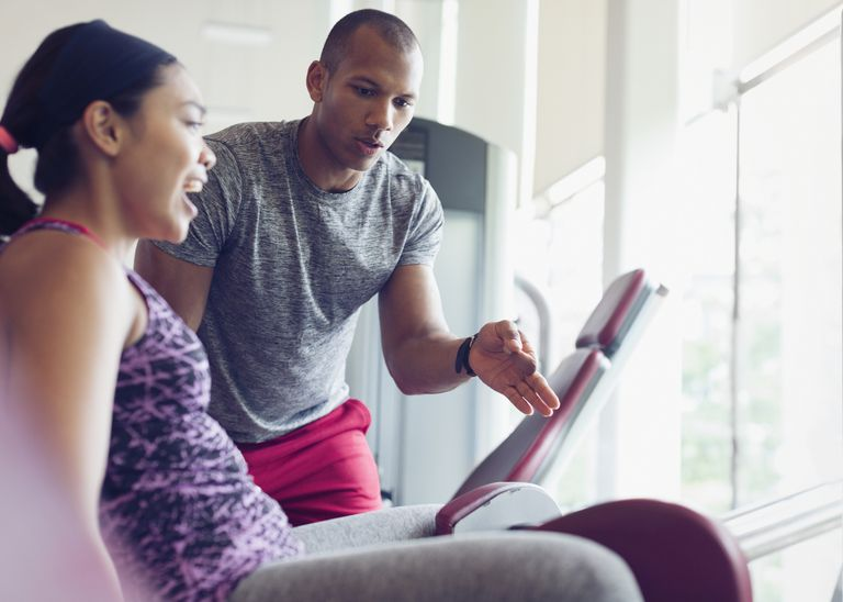 Personal trainer guiding woman on exercise equipment at gym