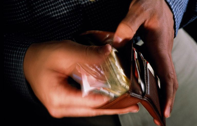Man leafing through wallet, close-up (blurred motion)
