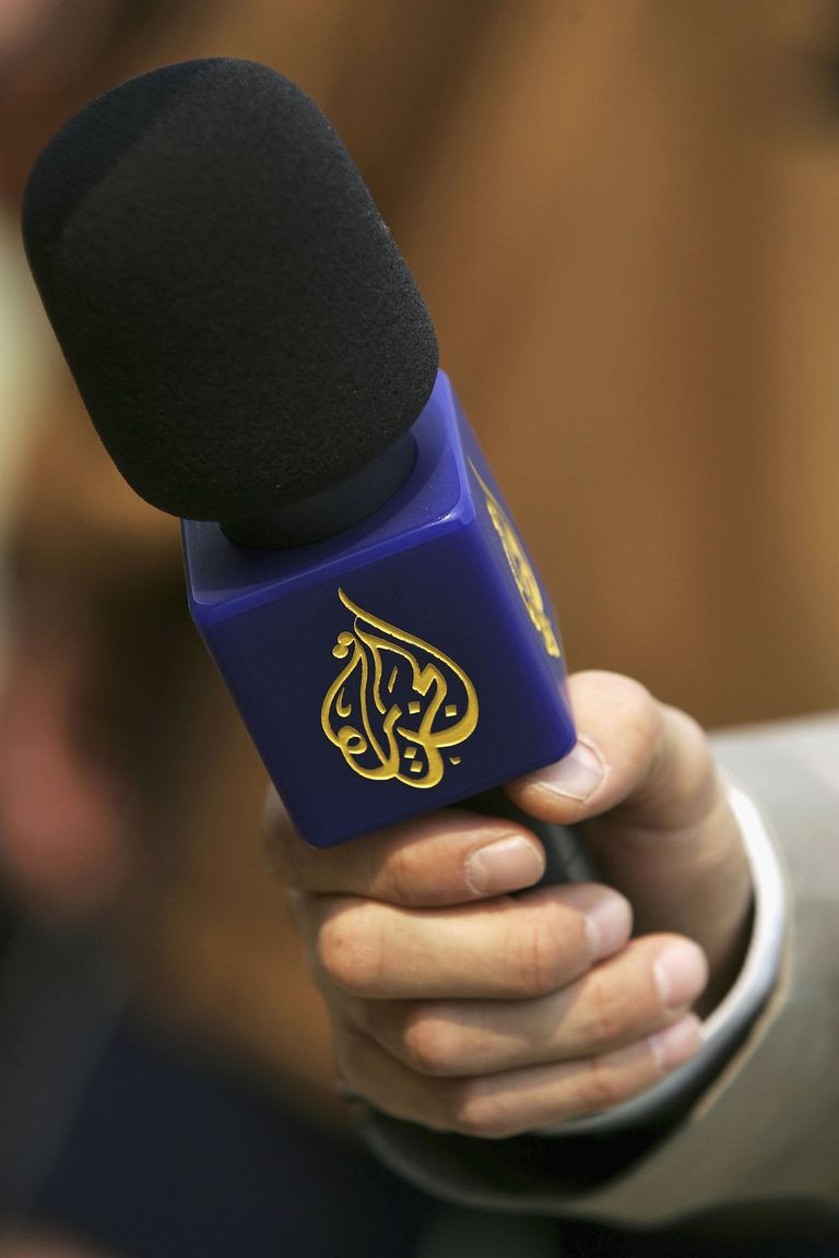 An Al Jazeera reporter holds a microphone.
