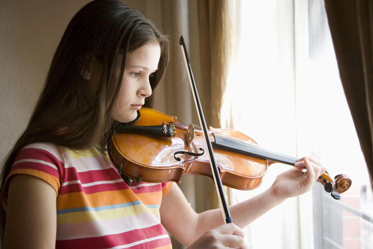 Girl (10-11) playing violin, looking out of window