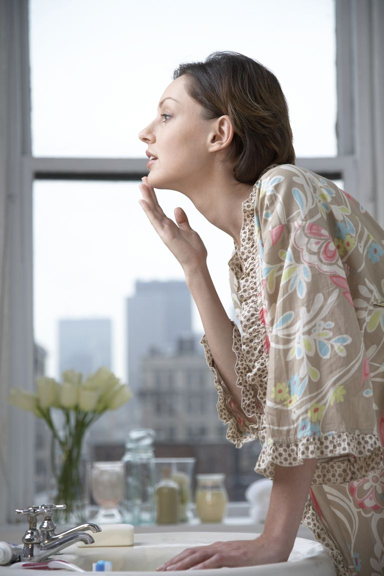 Mid adult woman touching chin and looking at mirror