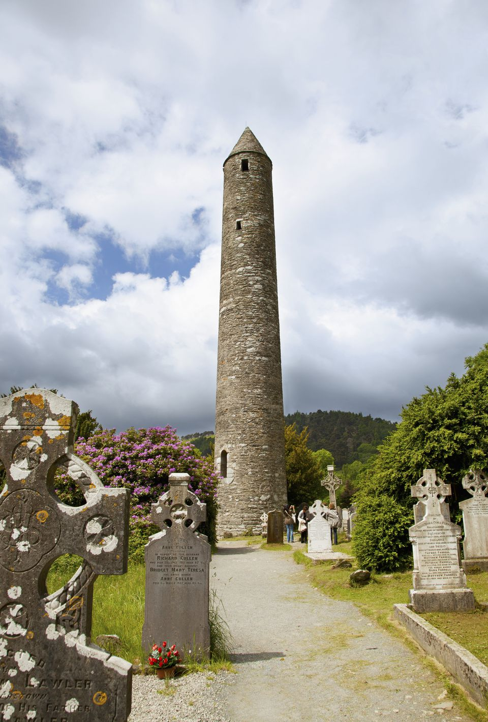 tombstones in a cemetery and a round tower on a 6th century monastic site