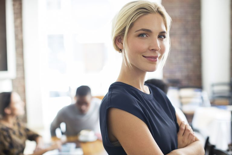female businesswoman smiling with people in the background