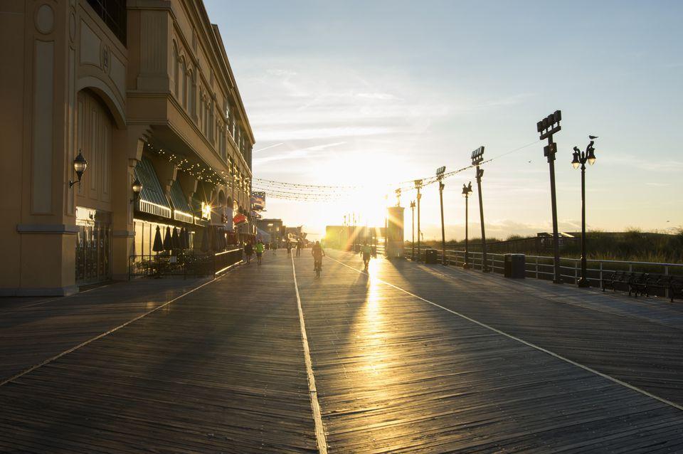 People on the Atlantic City boardwalk at sunrise.