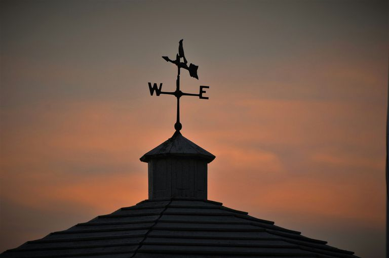 Low angle view of weather vane on roof against a cloudy sky at sunset.