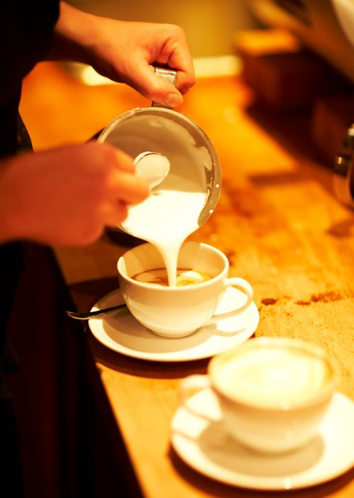 Hands pouring steamed milk into coffee cup.