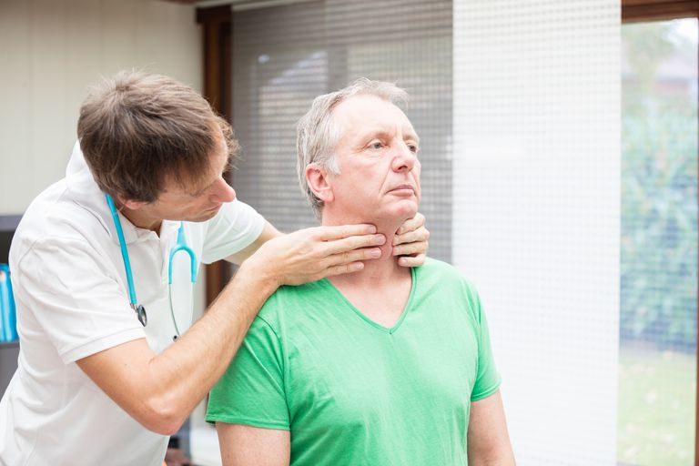Doctor checking thyroidea of mature patient