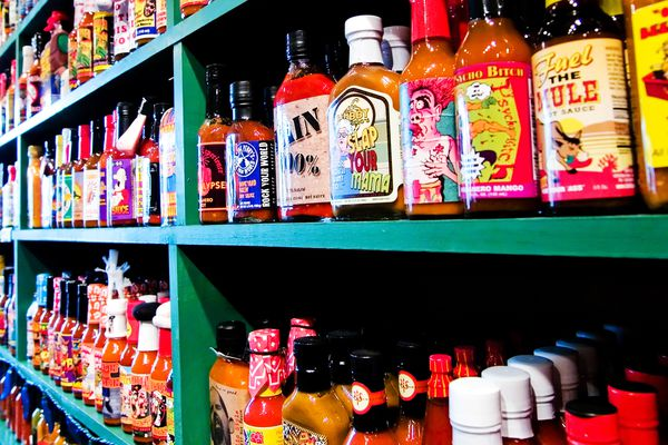 many different hot sauces on shelf