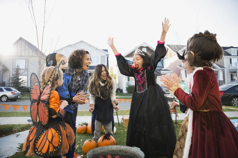 Exuberant girl in Halloween costume bobbing for apples